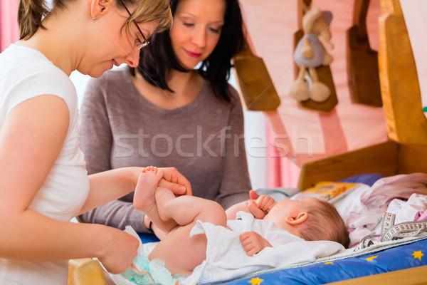 Midwife examining newborn baby Stock photo © Kzenon
