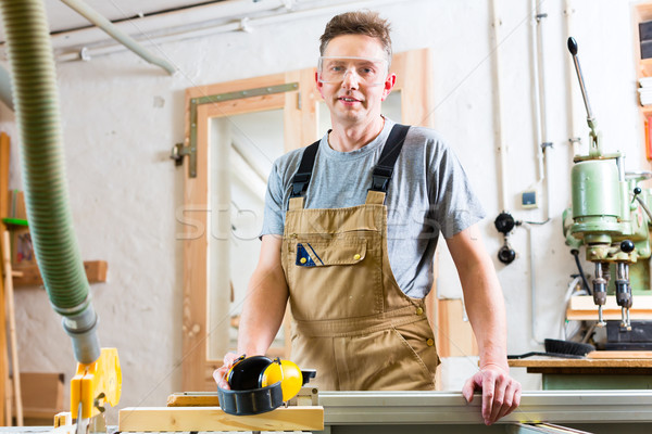 Carpenter using electric saw in carpentry Stock photo © Kzenon