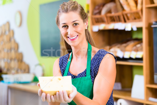 Saleswoman at counter offering cheese Stock photo © Kzenon
