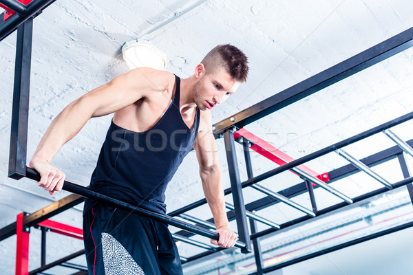Man at freestyle Calisthenics training in gym Stock photo © Kzenon