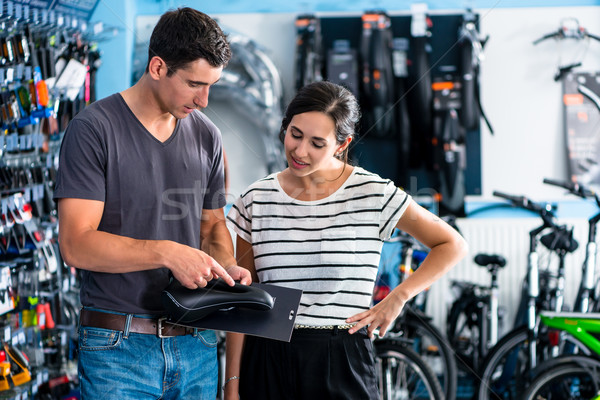 Woman buying parts in bike shop Stock photo © Kzenon