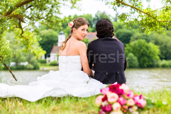 Bridal pair with bouquet on meadow at river Stock photo © Kzenon