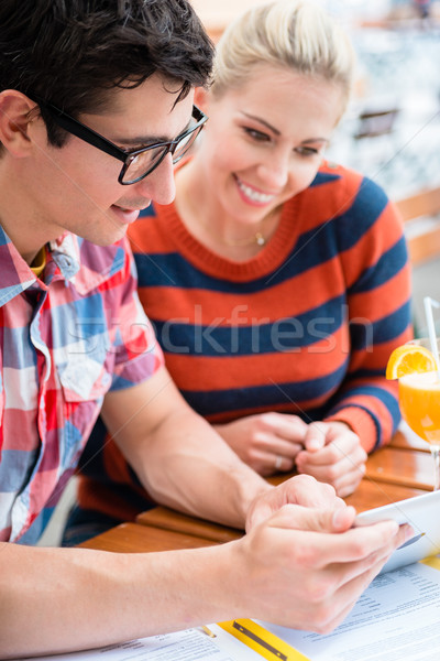 Couple in street cafe watching pictures of holidays Stock photo © Kzenon