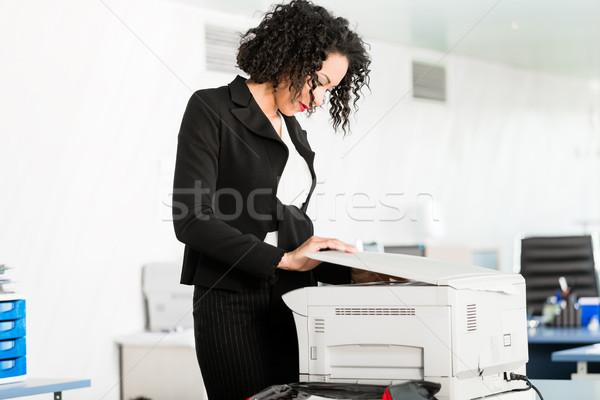 Businesswoman standing at the copying machine Stock photo © Kzenon