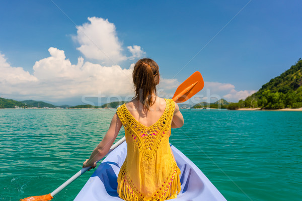 Young woman paddling a canoe during vacation in Flores Island, I Stock photo © Kzenon