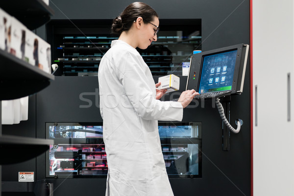 pharmacist using a computer while managing the drug stock in pha Stock photo © Kzenon