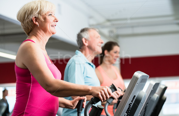 Seniors training on cross trainer with personal trainer at the g Stock photo © Kzenon
