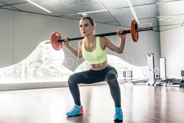 Determined woman holding a barbell behind the neck during functi Stock photo © Kzenon