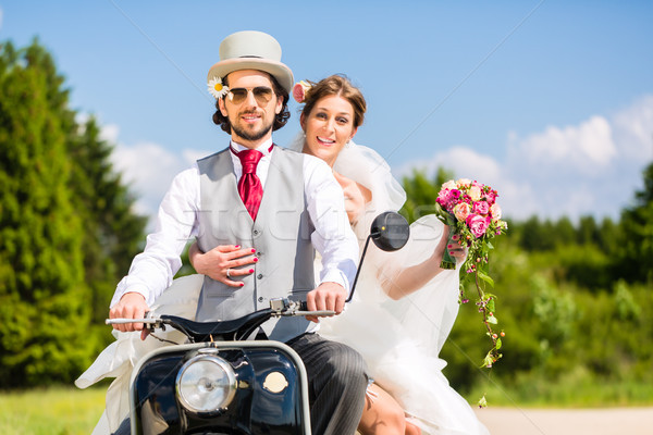 Bridal pair driving motor scooter wearing gown and suit Stock photo © Kzenon
