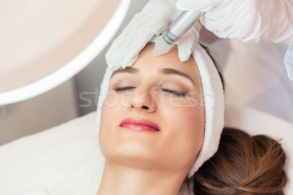 Close-up of the face of a beautiful woman smiling during facial treatment Stock photo © Kzenon