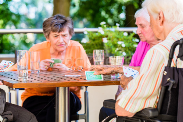 Group of seniors playing board game on terrace of retirement home Stock photo © Kzenon