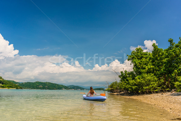 Young woman paddling during vacation in an idyllic travel destination Stock photo © Kzenon
