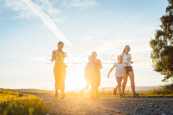 Playful family running and playing on a path in summer landscape Stock photo © Kzenon
