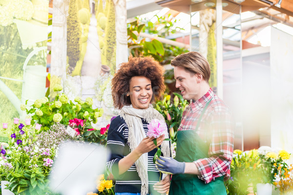 Cheerful female customer buying flowers at the advice of a helpful vendor Stock photo © Kzenon