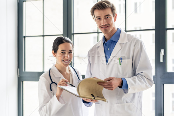 Two dedicated doctors smiling while holding a folder with medical records Stock photo © Kzenon