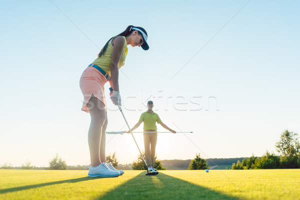 Fit woman exercising hitting technique during golf class with Stock photo © Kzenon