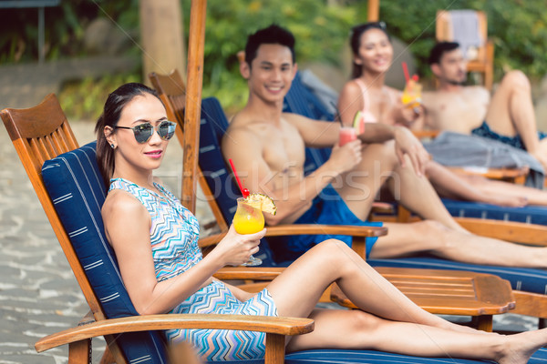 Beautiful woman enjoying a delicious cocktail at a trendy swimming pool Stock photo © Kzenon