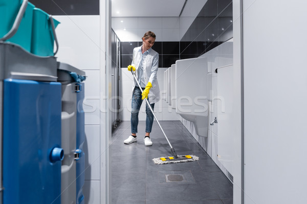 Cleaning lady mopping the floor in mens restroom Stock photo © Kzenon