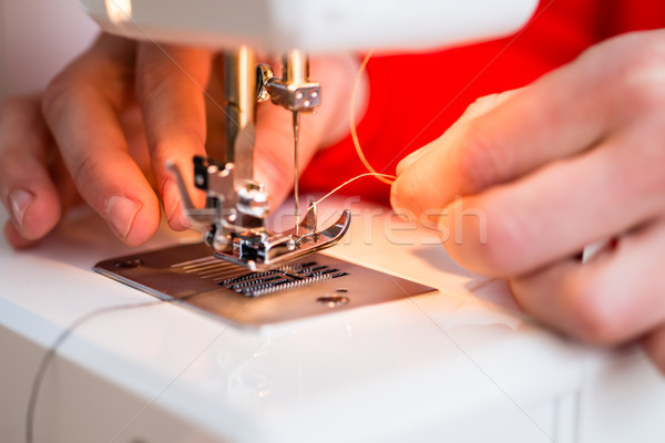 Stock photo: Person inserting thread in to a needle
