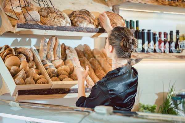 Shop assistant sorting bread to be sold Stock photo © Kzenon