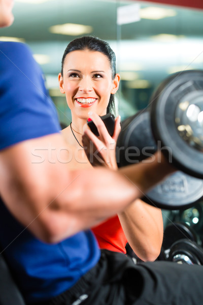 Stock photo: Personal Trainer in gym and dumbbell training
