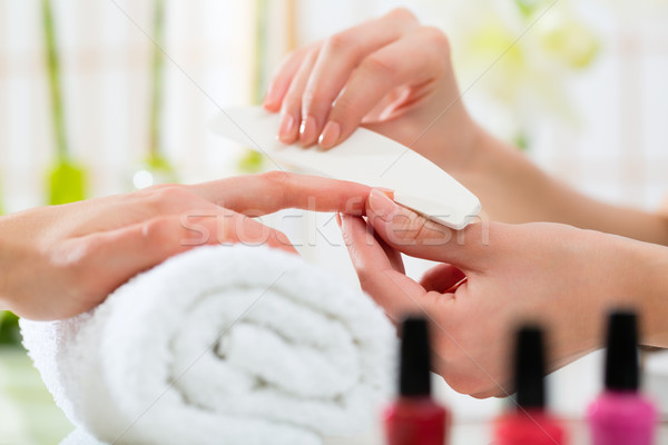 Stock photo: Woman in nail salon receiving manicure