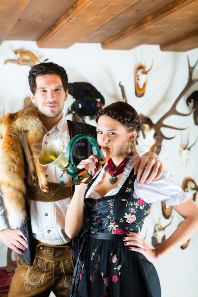 Hunter and woman in an alpine mountain hut with horn Stock photo © Kzenon