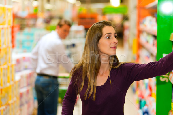 Stock photo: Man and woman in supermarket with shopping cart