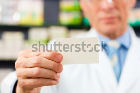 Pharmacist with business card in pharmacy Stock photo © Kzenon