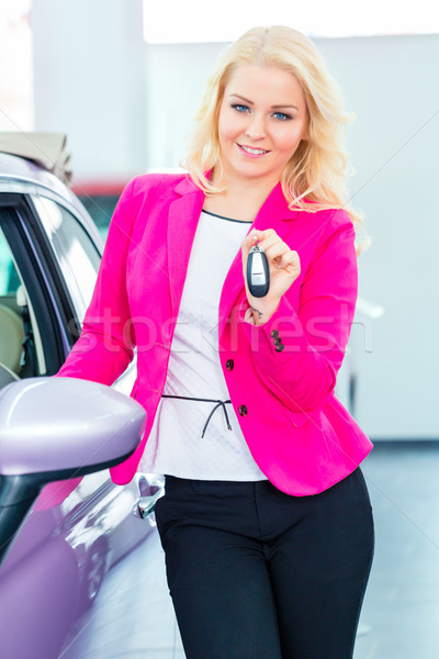 Woman buying new car at dealership showing key Stock photo © Kzenon