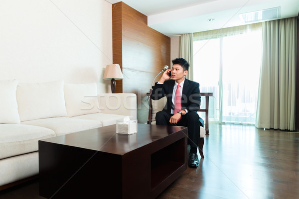 Chinese Businessman on business trip in hotel suite Stock photo © Kzenon