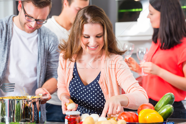 Friends cooking pasta and meat in domestic kitchen Stock photo © Kzenon