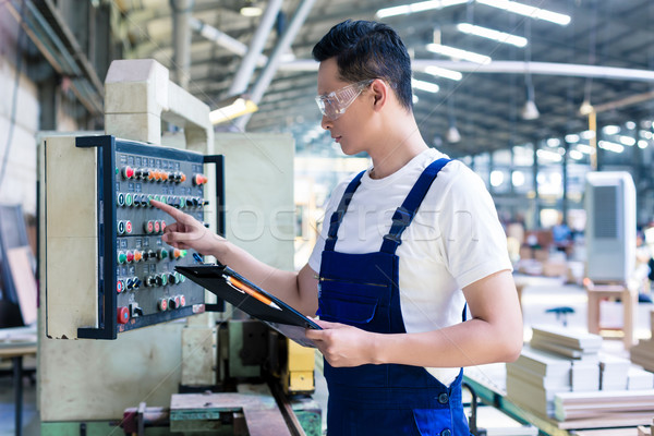Worker pressing buttons on CNC machine in factory Stock photo © Kzenon