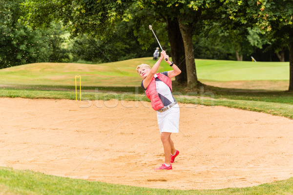 Senior woman at golf having stroke in sand bunker Stock photo © Kzenon
