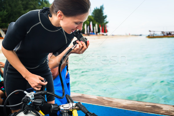 Woman diver testing regulator before scuba diving Stock photo © Kzenon