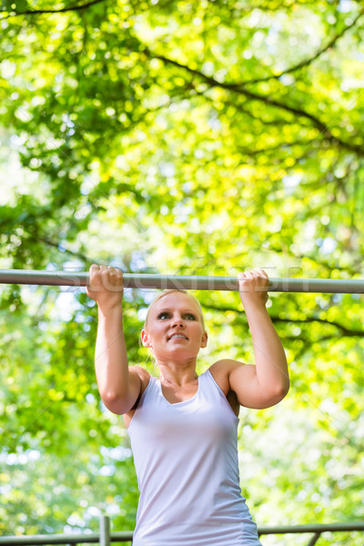 Woman exercising at high bar for better outdoor fitness Stock photo © Kzenon