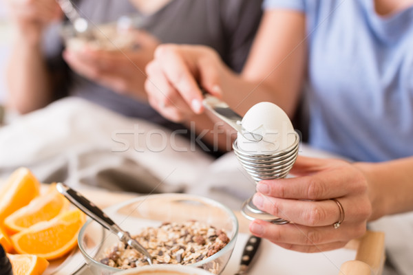 Woman opening a boiled egg for breakfast Stock photo © Kzenon