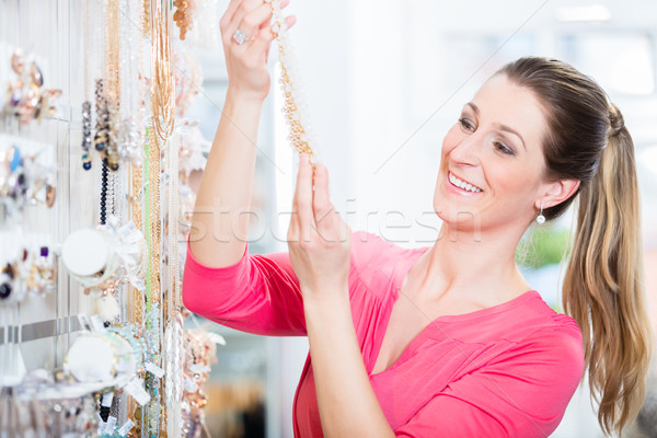 Woman shopping in store looking at trinket necklace Stock photo © Kzenon