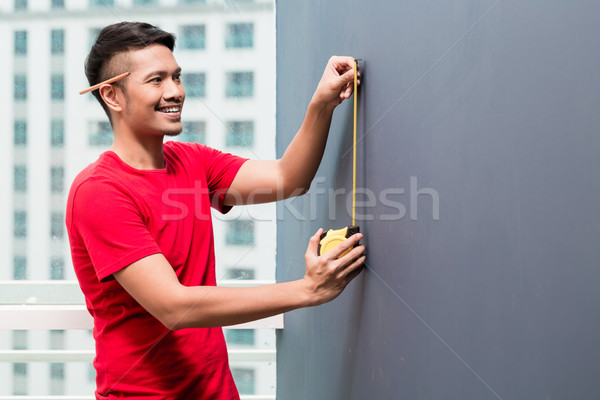 Young indonesian man sizing with tape measure Stock photo © Kzenon