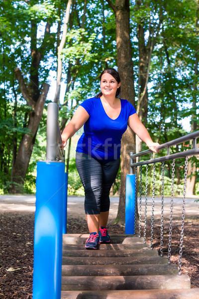 Overweight woman in climbing park doing sport Stock photo © Kzenon