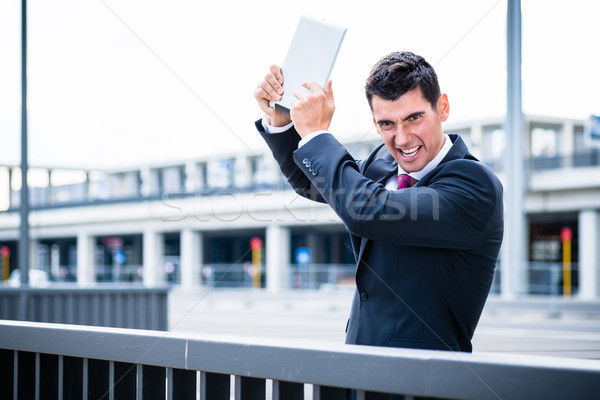 Angry business man with tablet computer Stock photo © Kzenon