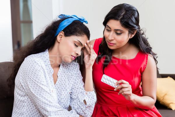 Woman giving medication against headache Stock photo © Kzenon