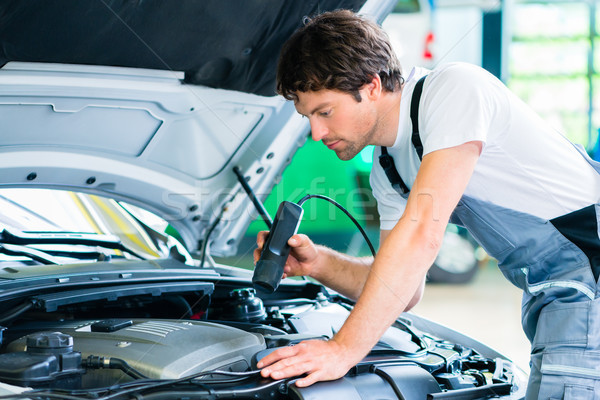 Mechanic with diagnostic tool in car workshop Stock photo © Kzenon