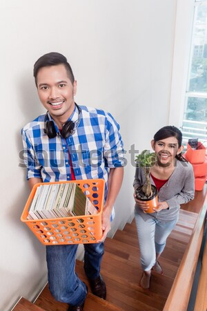 Young asian couple carrying belongings to new apartment Stock photo © Kzenon