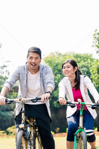 Young Asian couple laughing together while riding bicycles  Stock photo © Kzenon