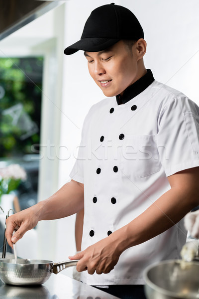 Chef cooking in a commercial kitchen Stock photo © Kzenon