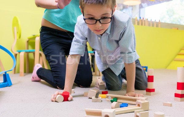 Pre-school boy wearing eyeglasses while playing with wooden toys Stock photo © Kzenon