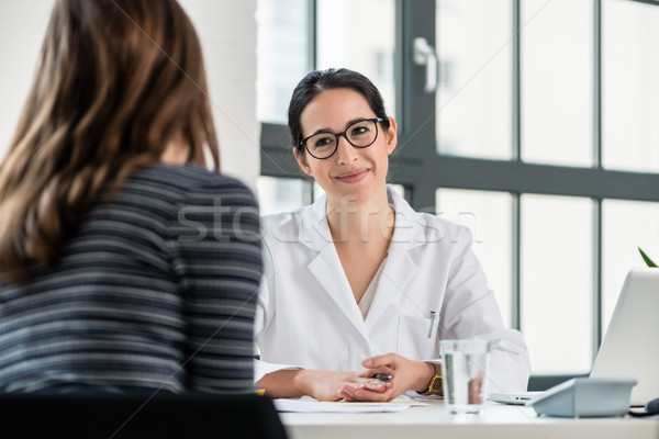 Female physician listening to her patient during consultation Stock photo © Kzenon