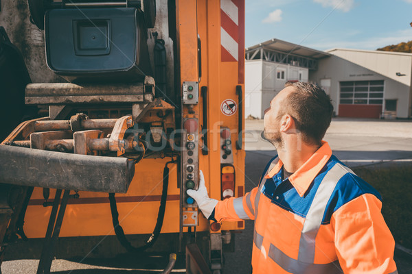 Worker emptying dustbin into waste vehicle Stock photo © Kzenon