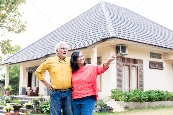 Happy elderly couple showing thumbs up in front of their new house Stock photo © Kzenon